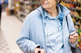 Senior woman with shopping basket in supermarket