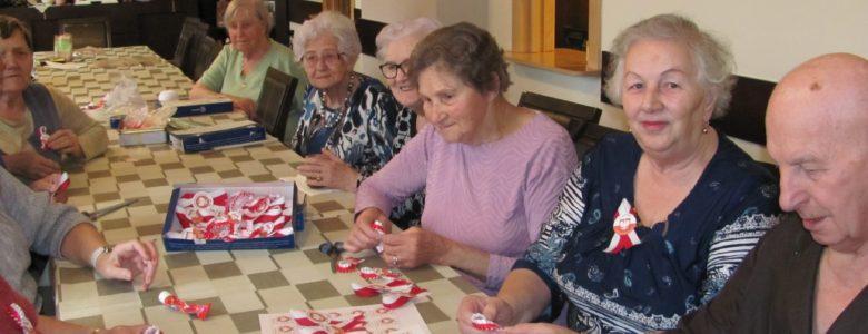 Seniorzy wykonują biało – czerwone kotyliony